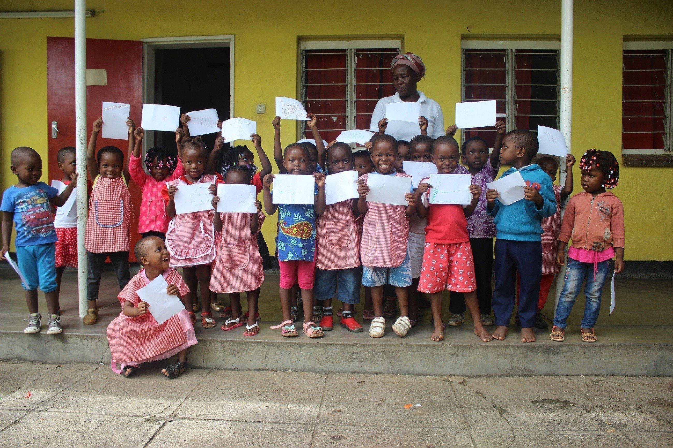 Un gruppo di bambini con dei disegni in mano di fronte a una casa.