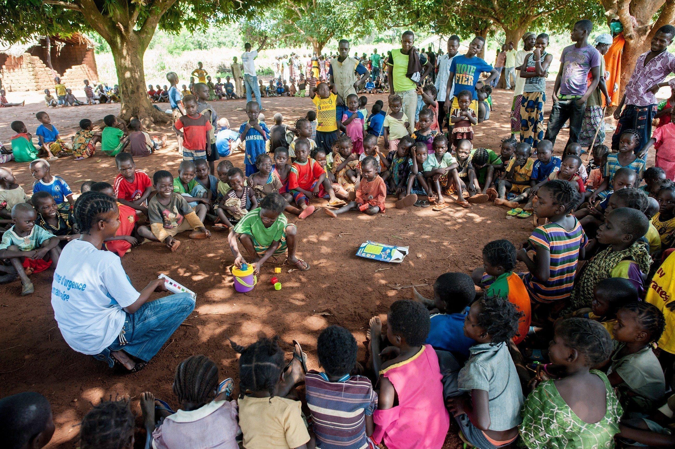 Bambini seduti in cerchio con l'assistente di SOS Villaggi dei Bambini.