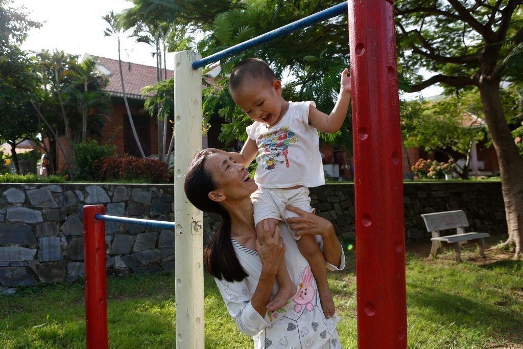Un bambino insieme alla mamma accanto alla struttura per arrampicarsi.