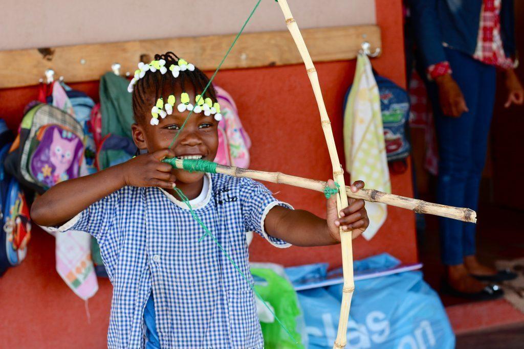 Bambino gioca con arco e freccia di legno.