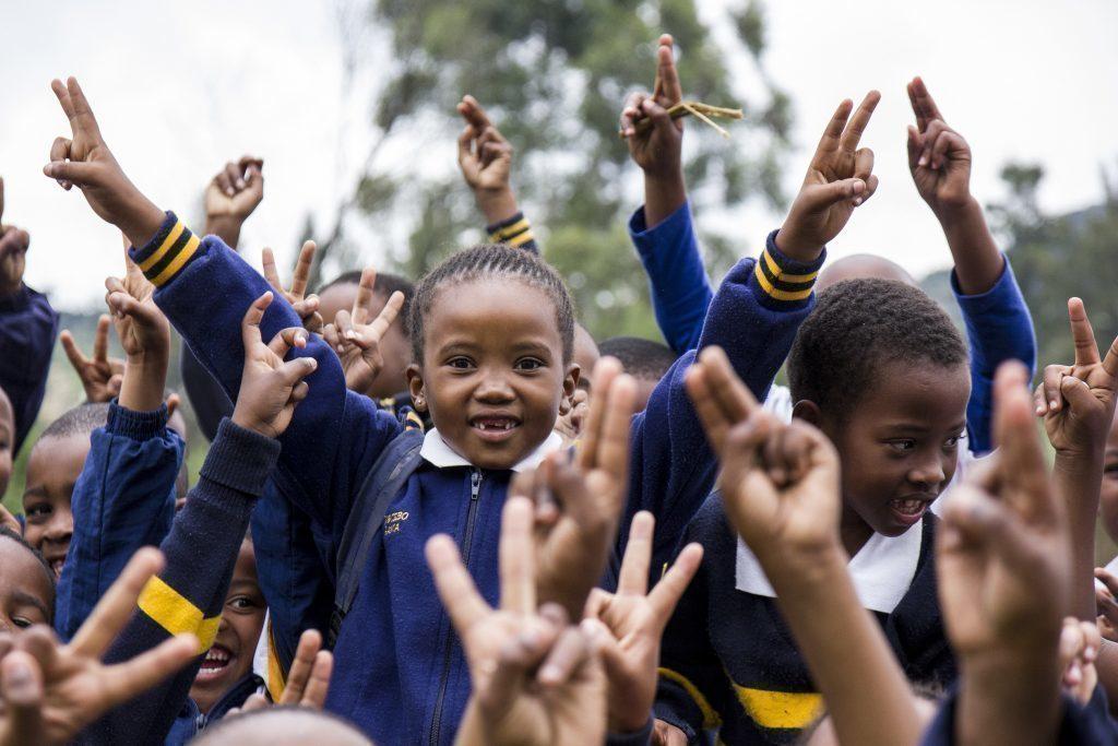 Mädchen in Schuluniform. Viele Hände mit Peace-Zeichen.