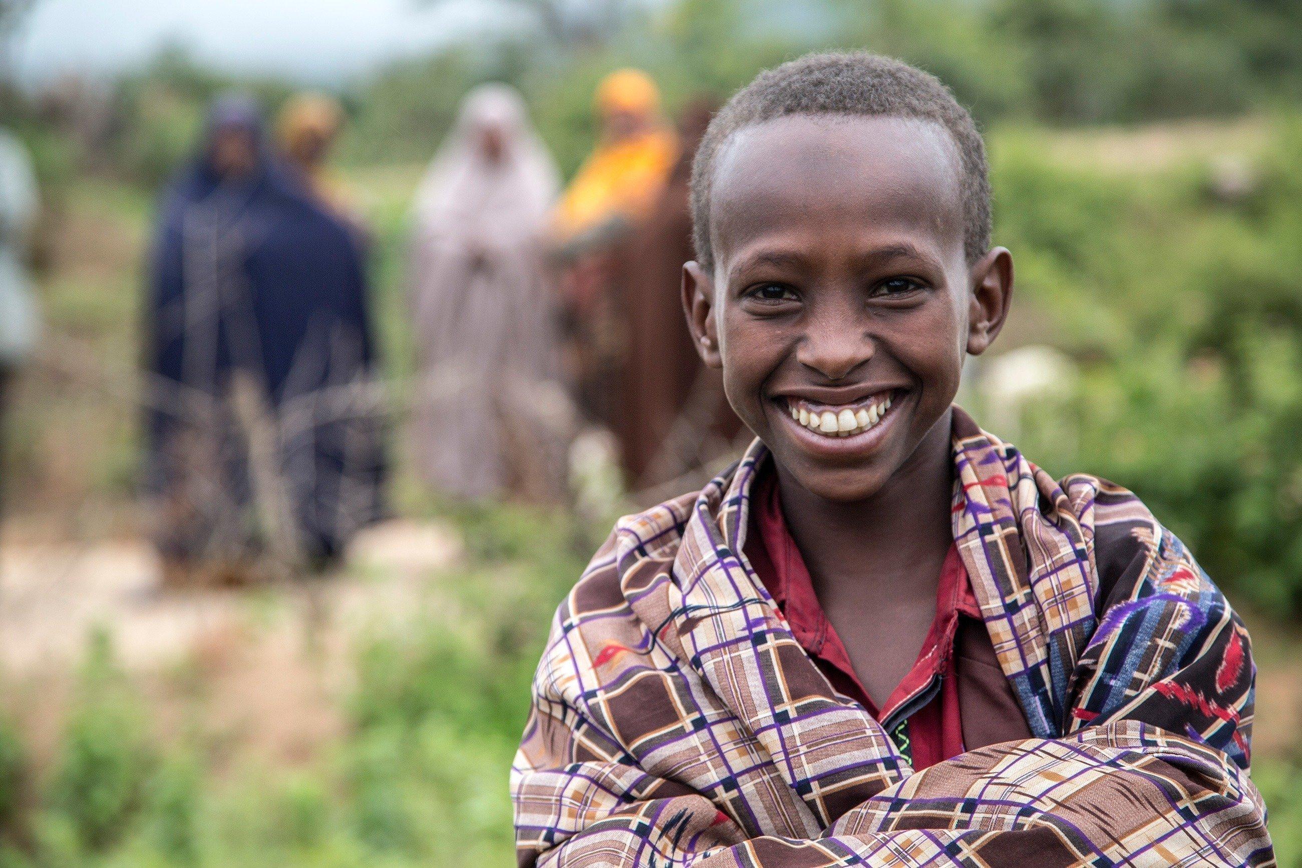 Bambino africano sorride alla fotocamera.