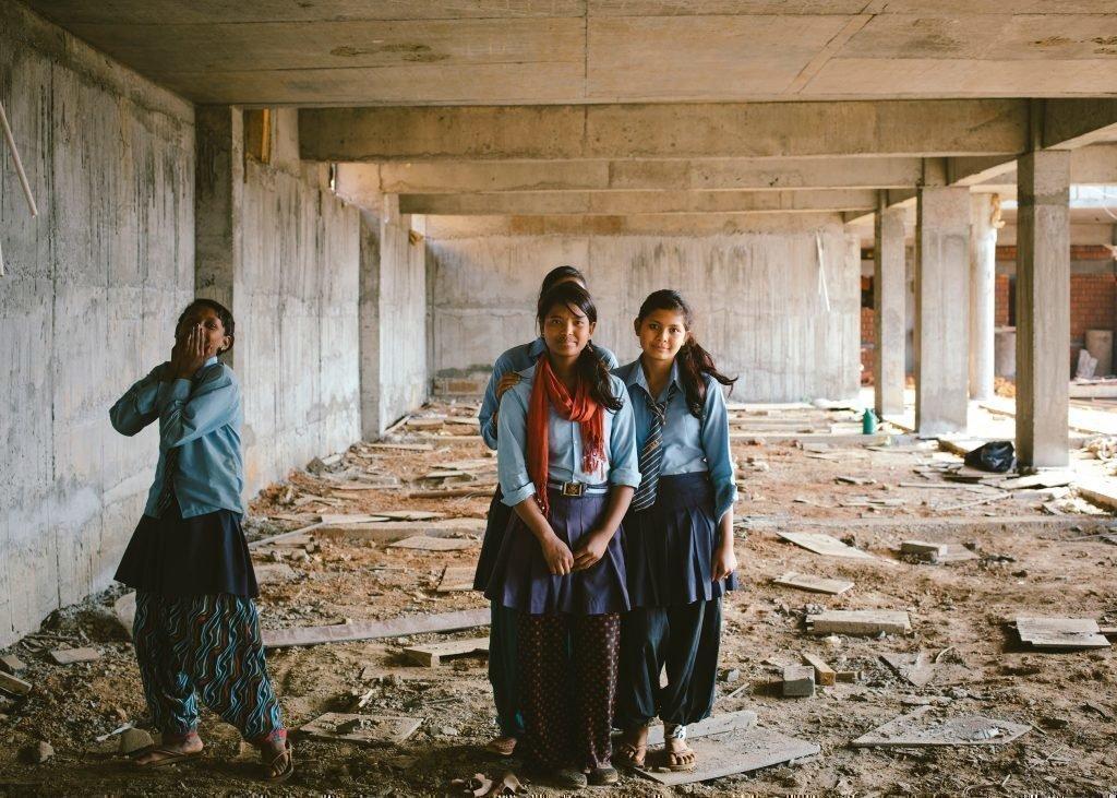 Quattro bambine ridono tra le macerie di una casa.