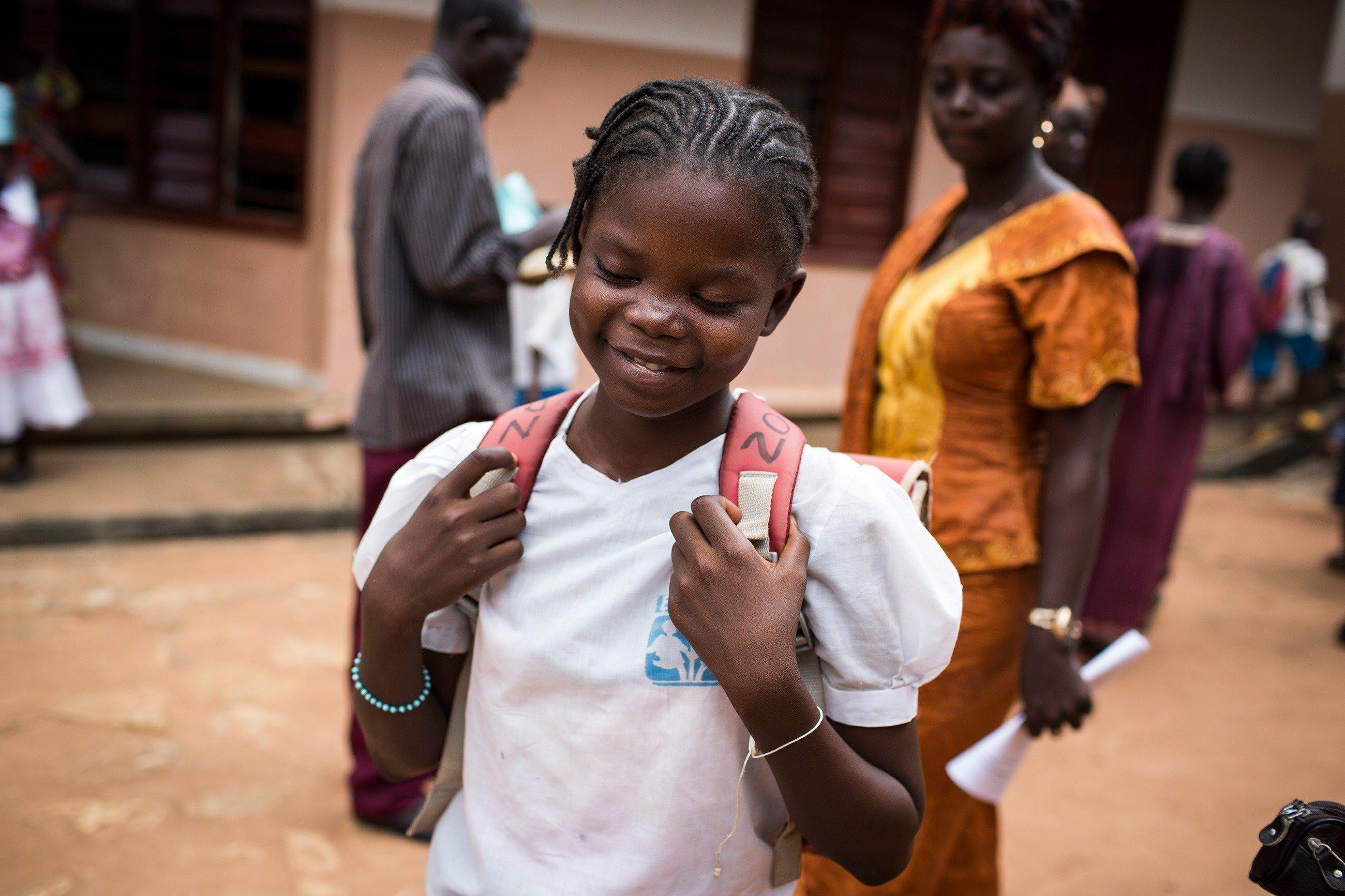 Bambina sorridente che si reca a scuola.