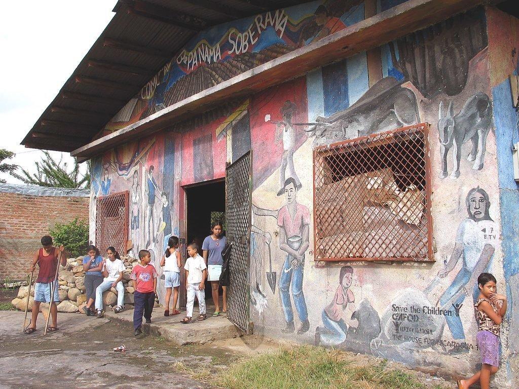 Kinder vor einem bemaltem Haus.
