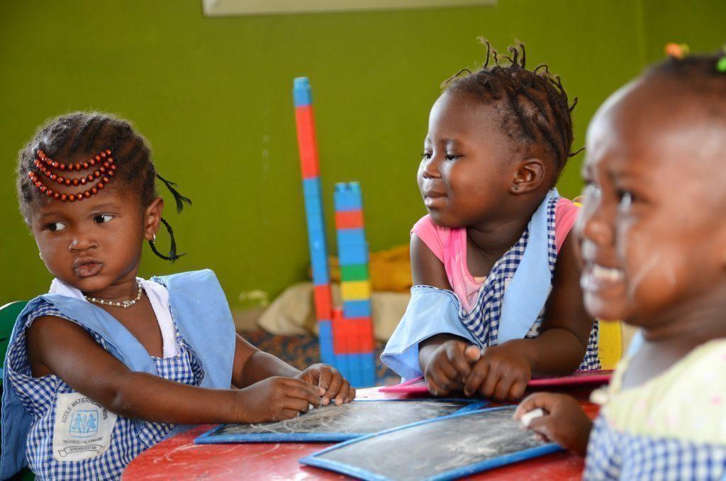 Tre bambine giocano a un tavolo.