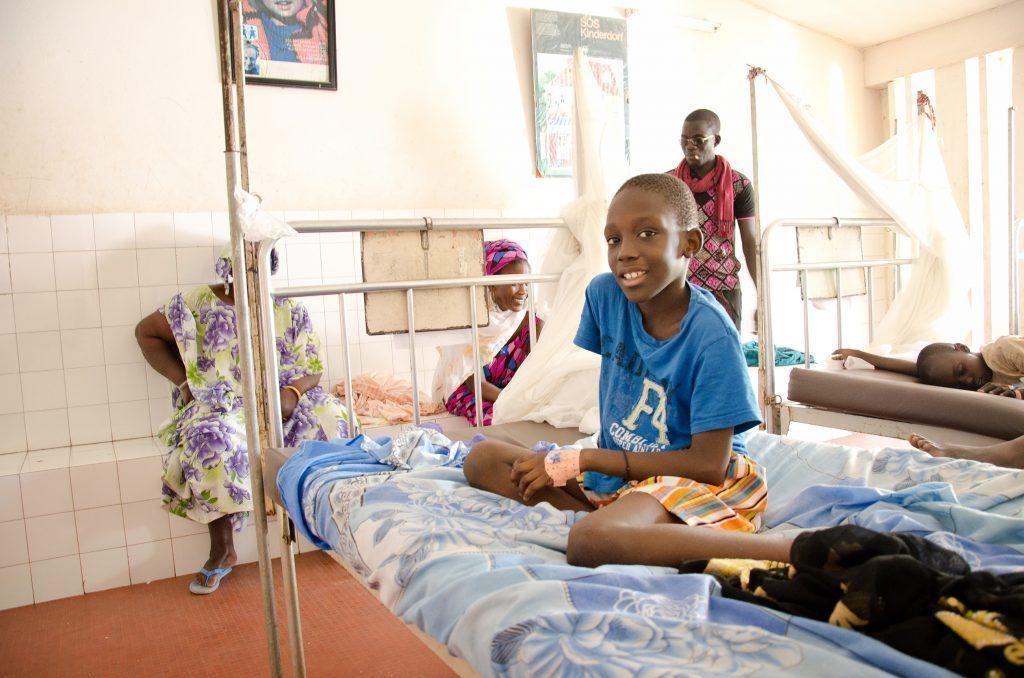 Un bambino sorridente in un letto d'ospedale.