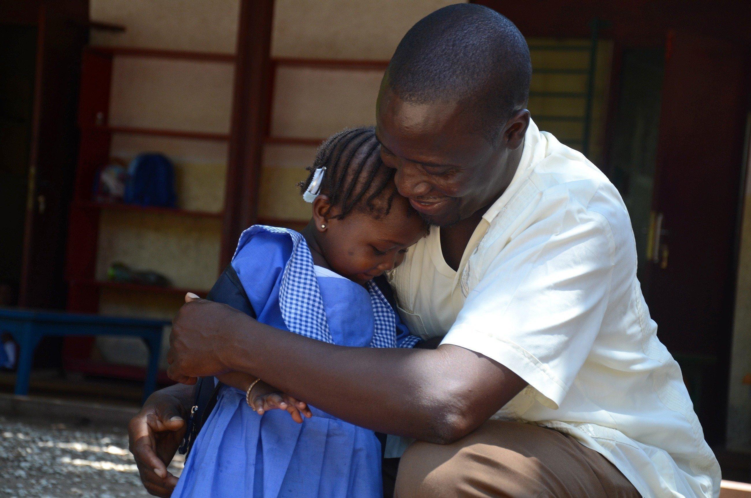 SOS-Kinderdorf Vater umarmt kleines Mädchen herzlich.