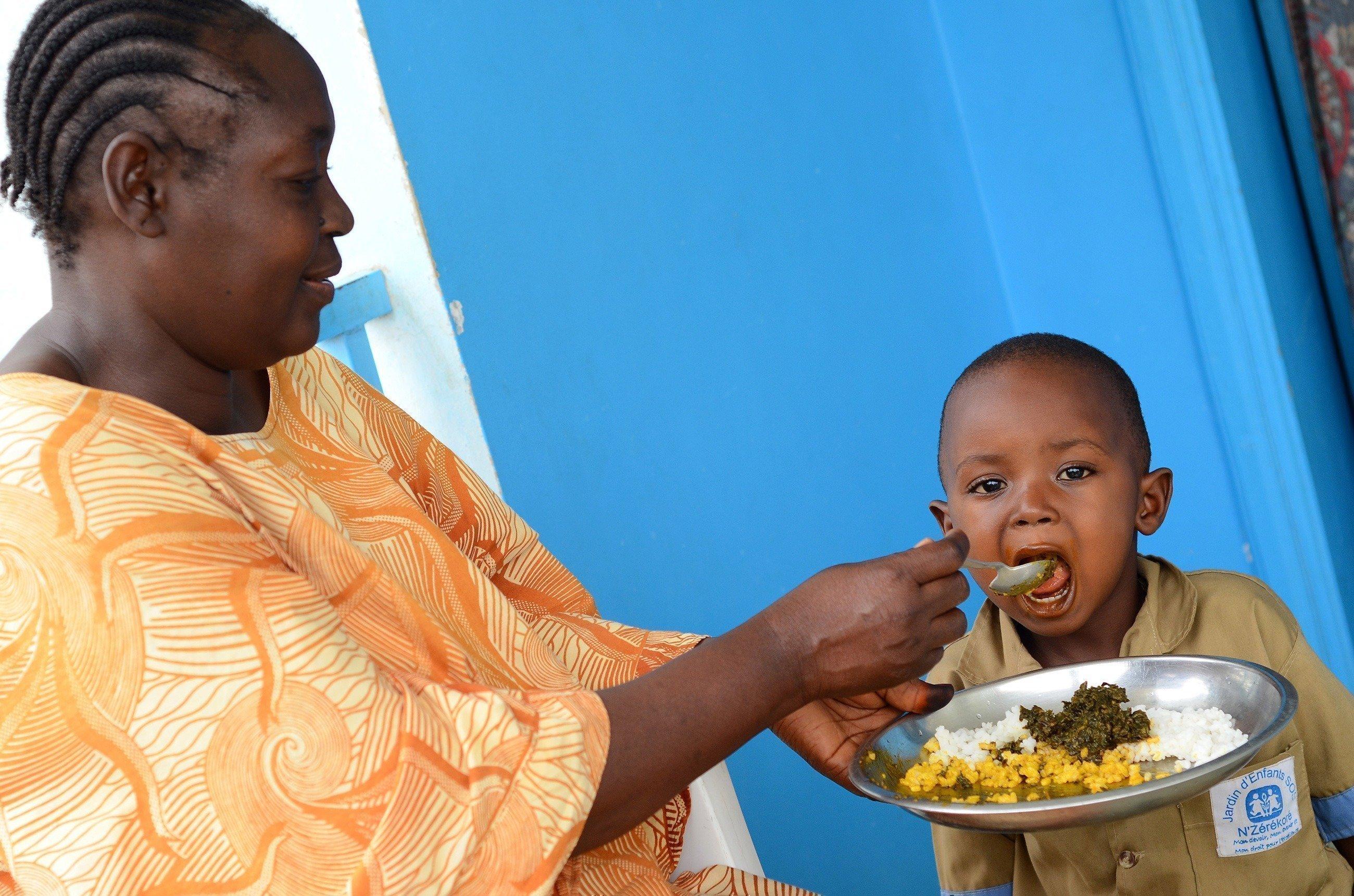 Una mamma di un villaggio dei bambini SOS che dà da mangiare a un bambino.