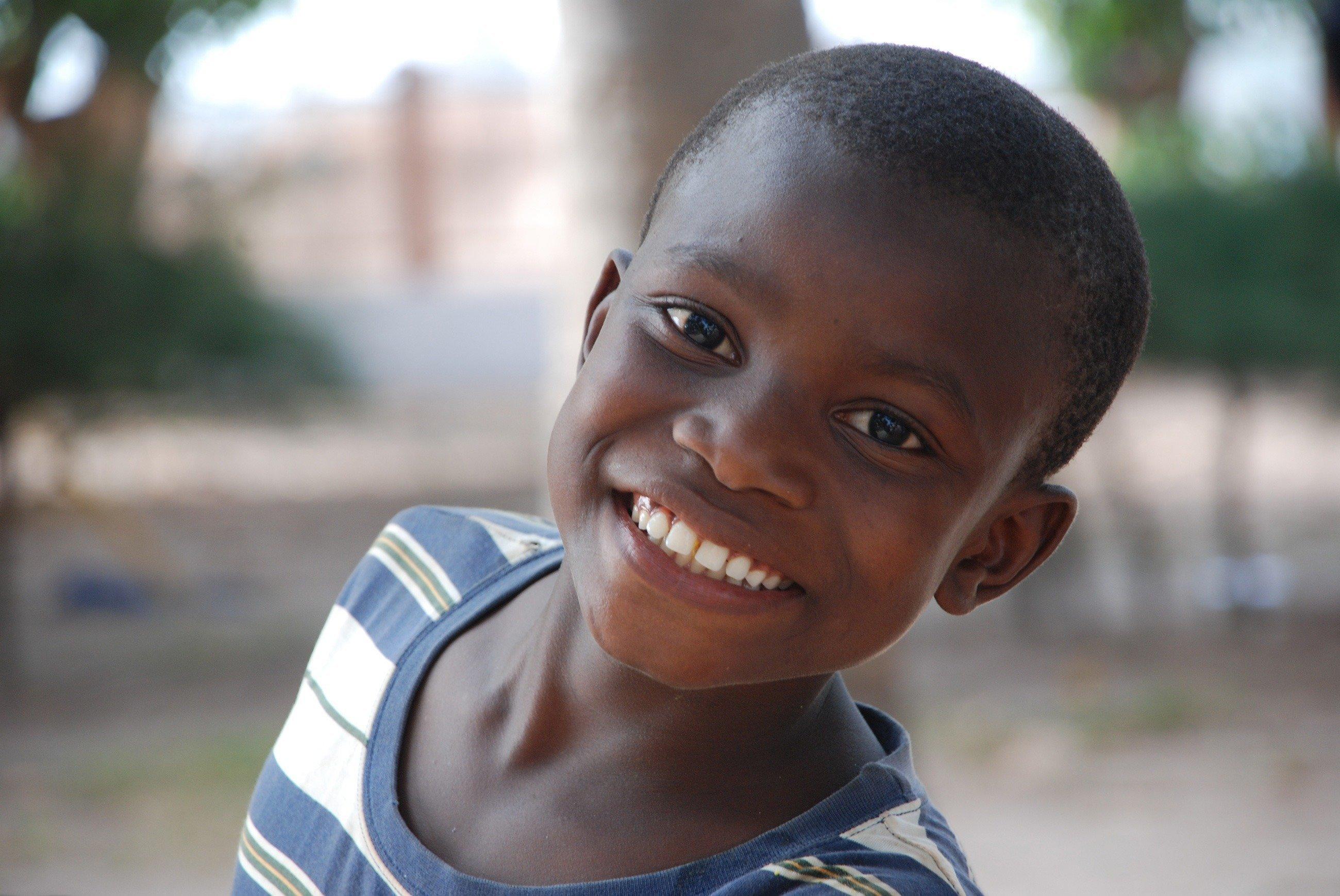 Un bambino allegro sorride all'obiettivo.