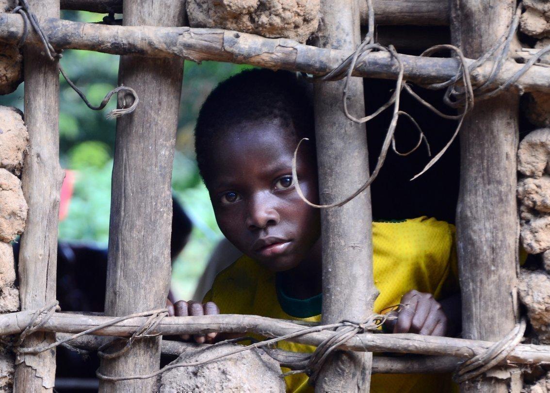 Un bambino africano guarda attraverso una ringhiera.