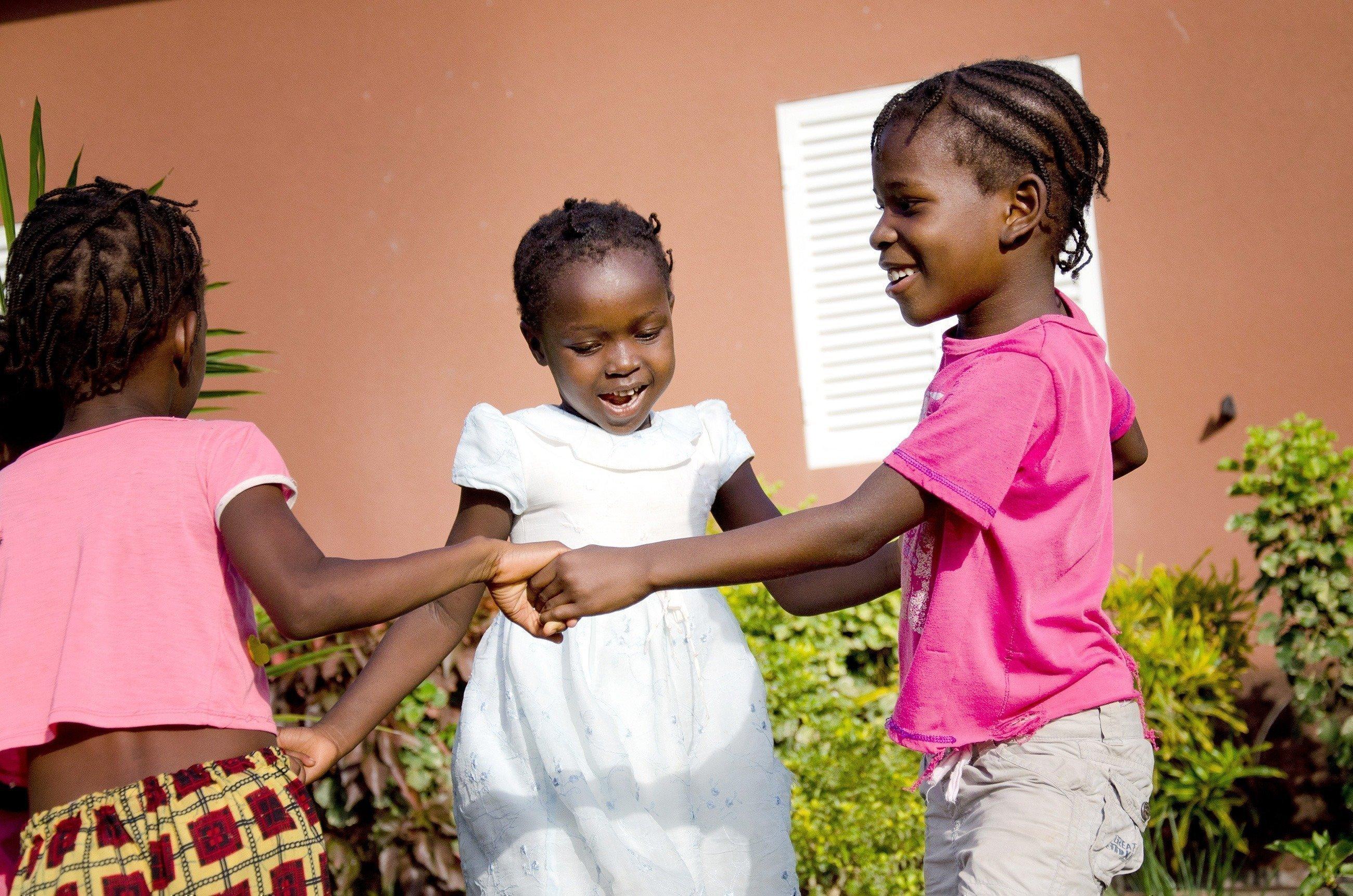 Tre ragazze ballano in cerchio.