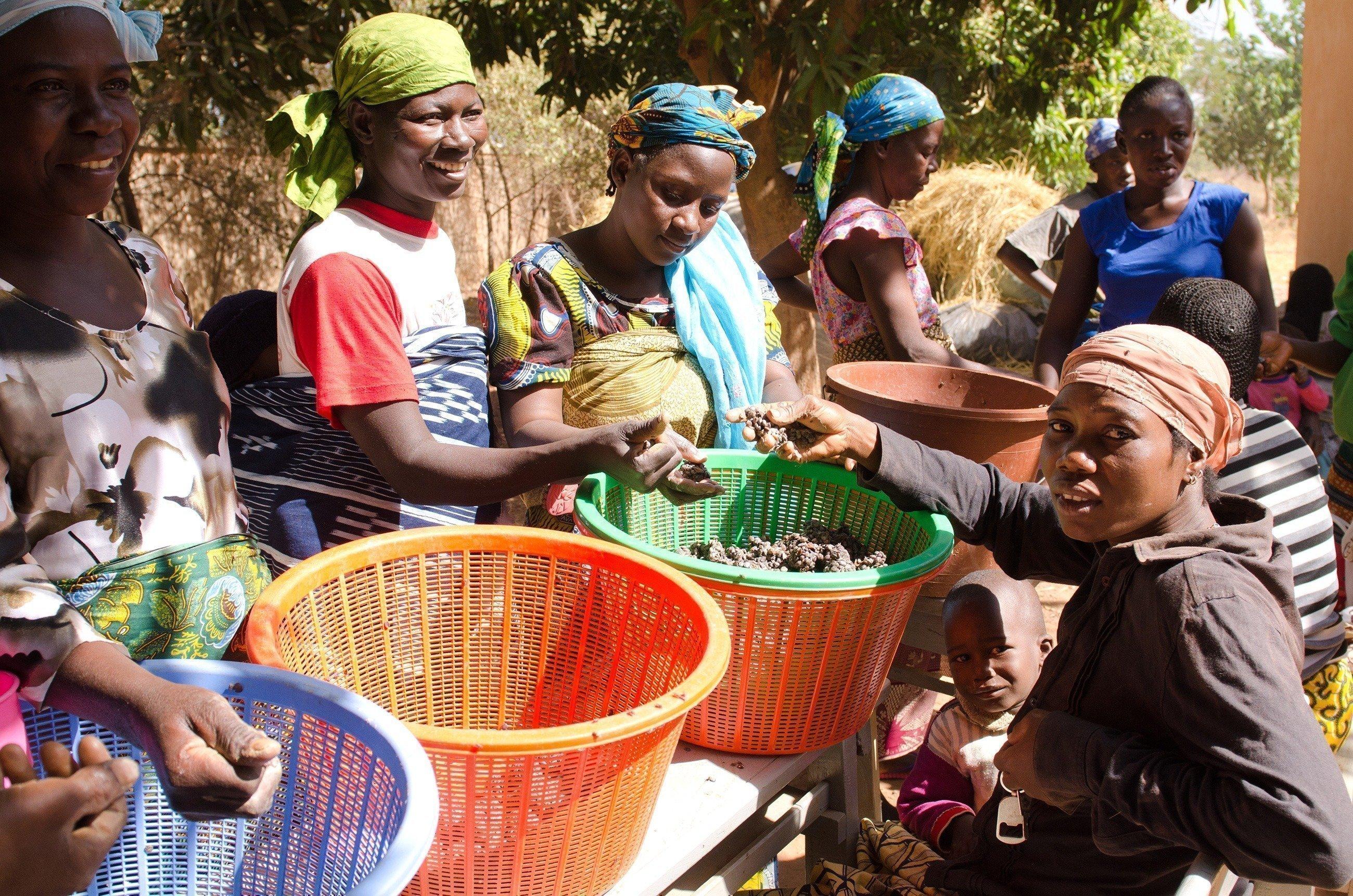 Un gruppo di donne con ceste piene di verdura.