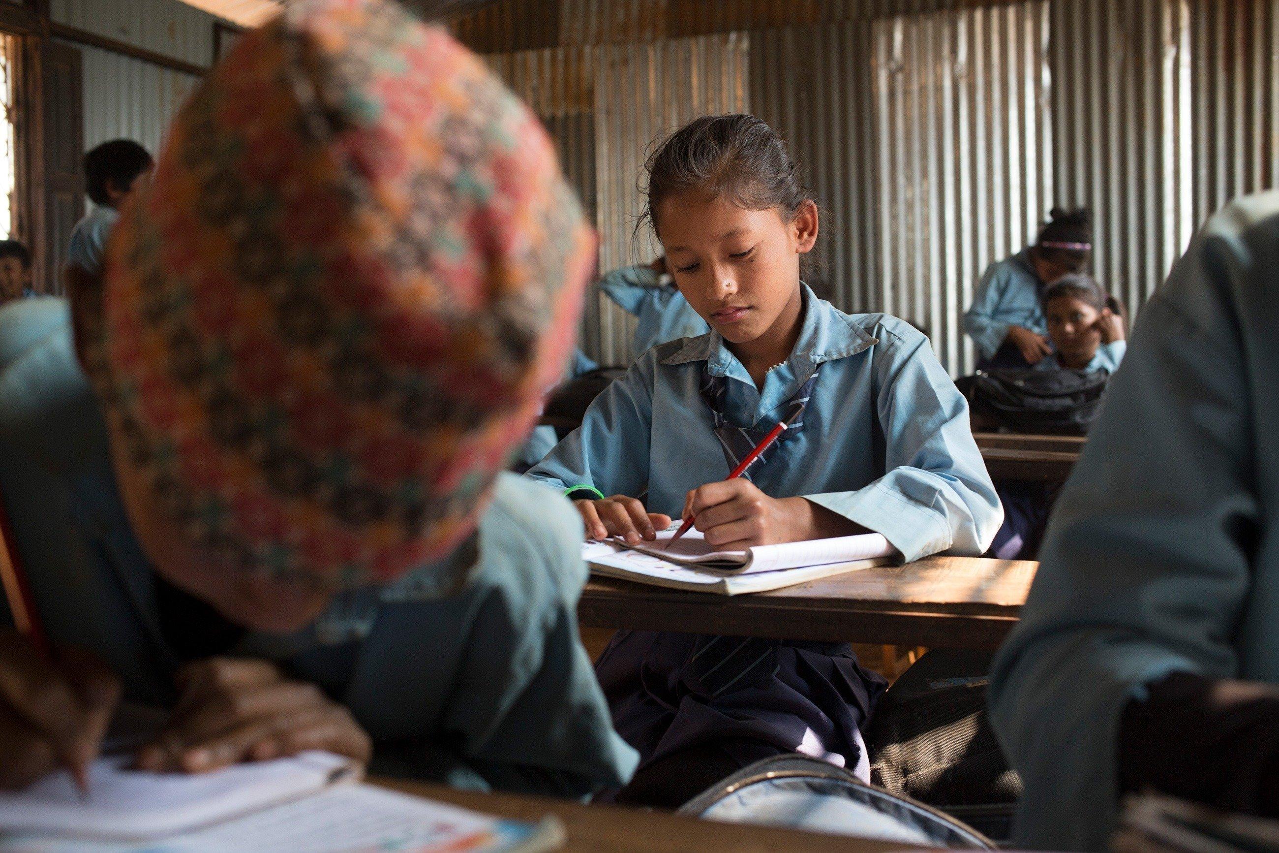 Bambina nepalese siede a scuola e scrive nel proprio quaderno.