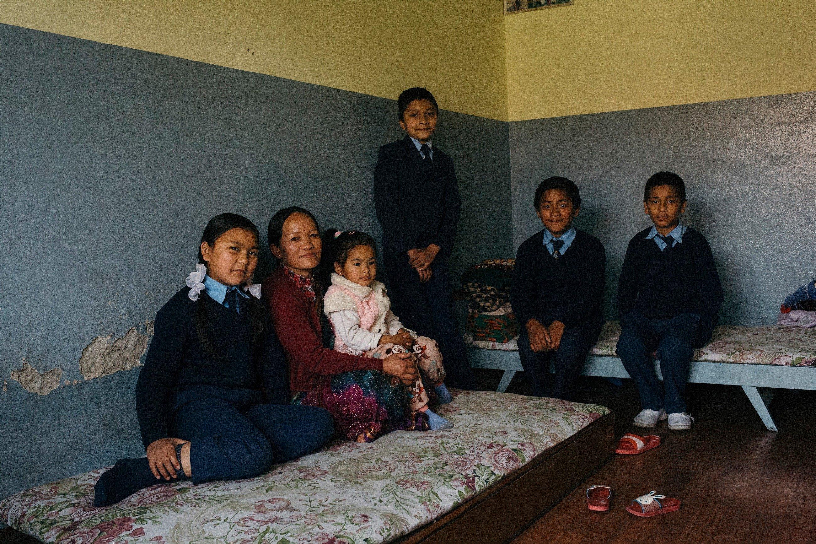 Una famiglia siede in una stanza su letti provvisori.