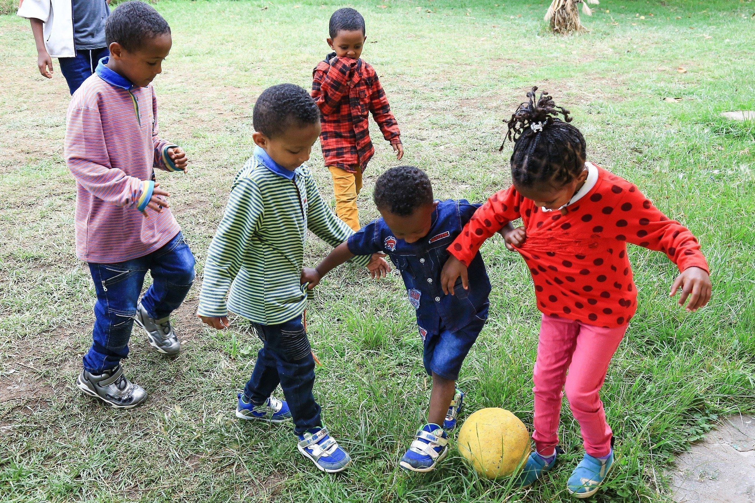 Bambini africani giocano a calcio.