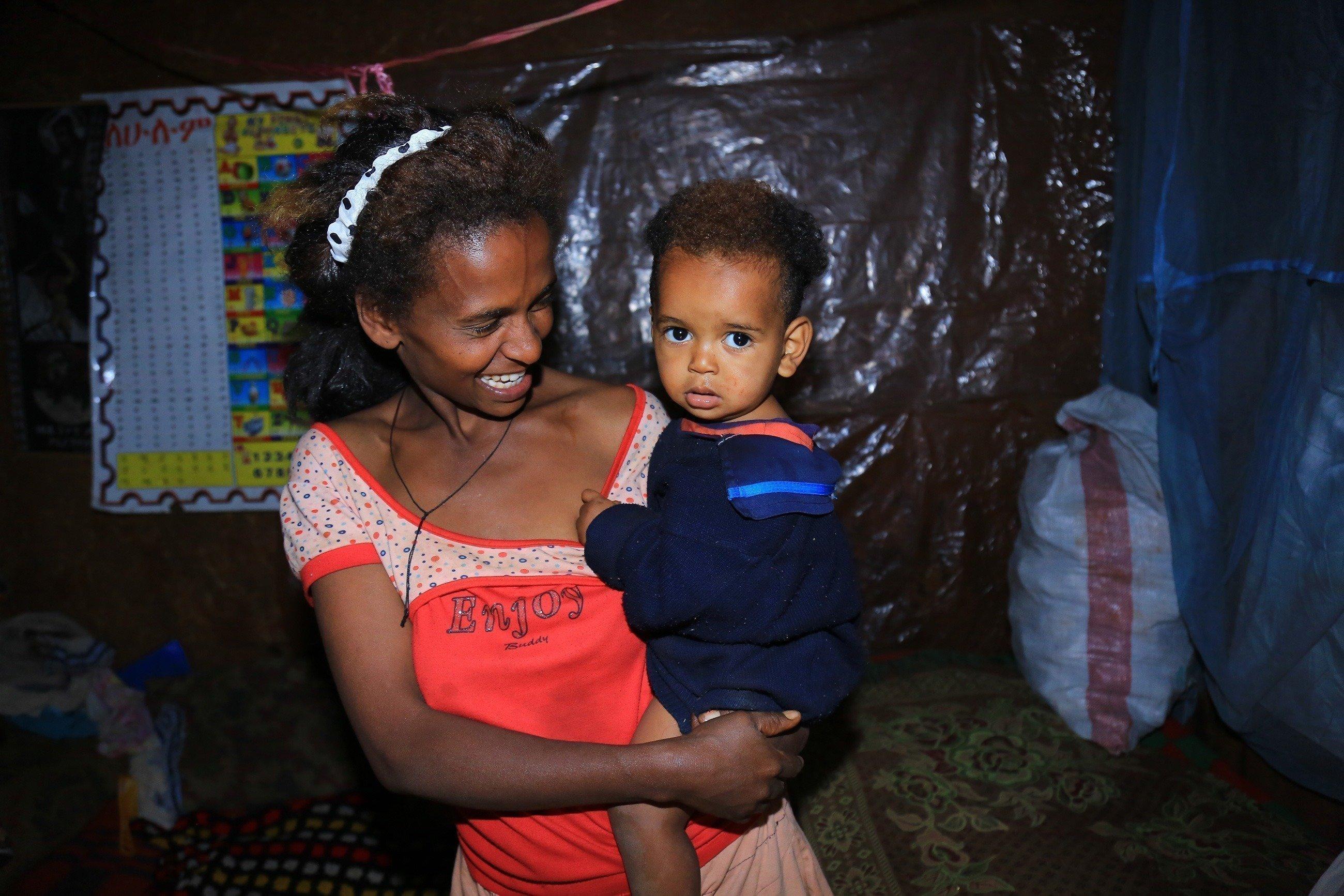 Madre tiene bambino africano in braccio e sorride.