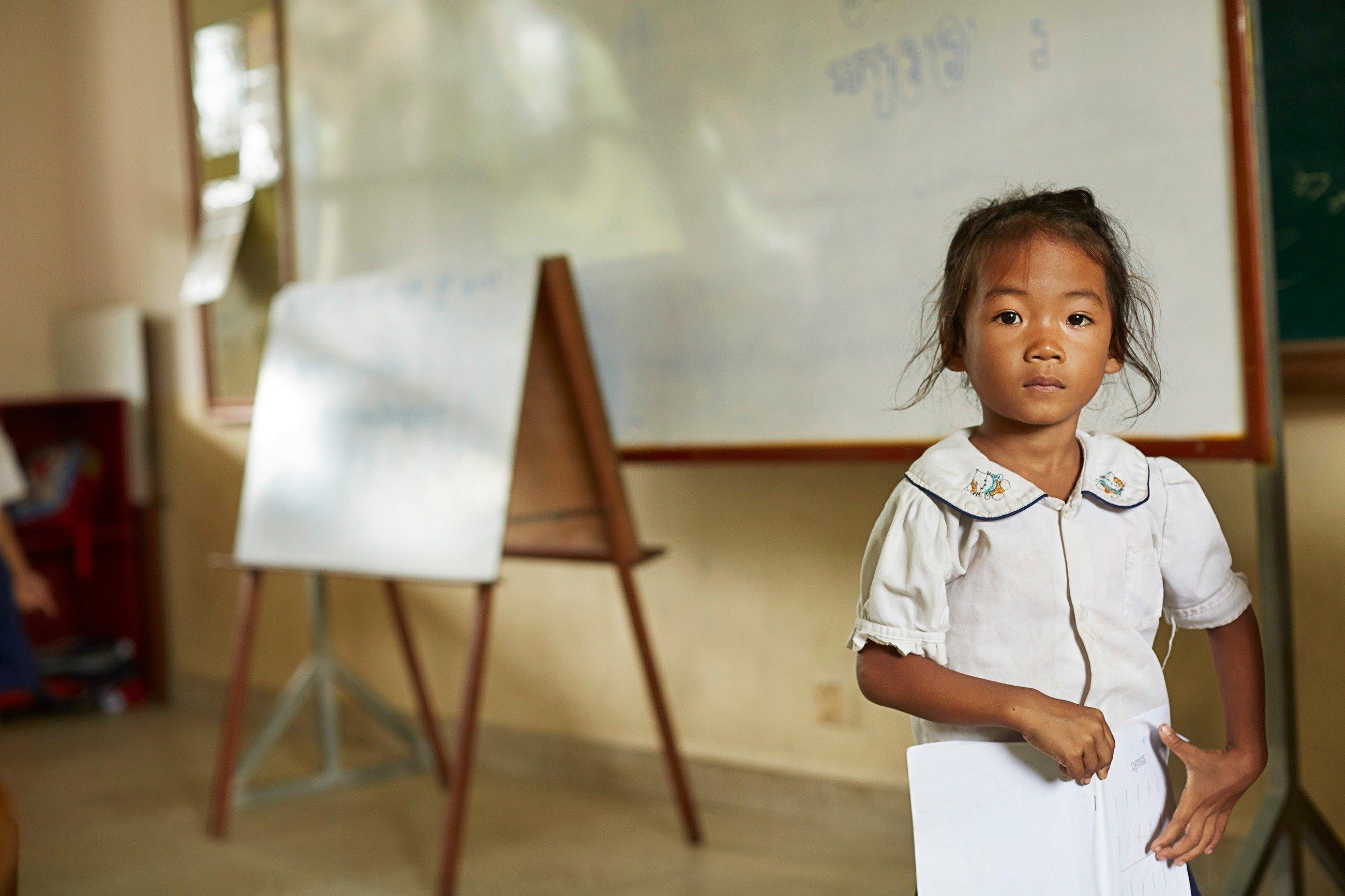 Bambina in piedi davanti a una lavagna bianca.