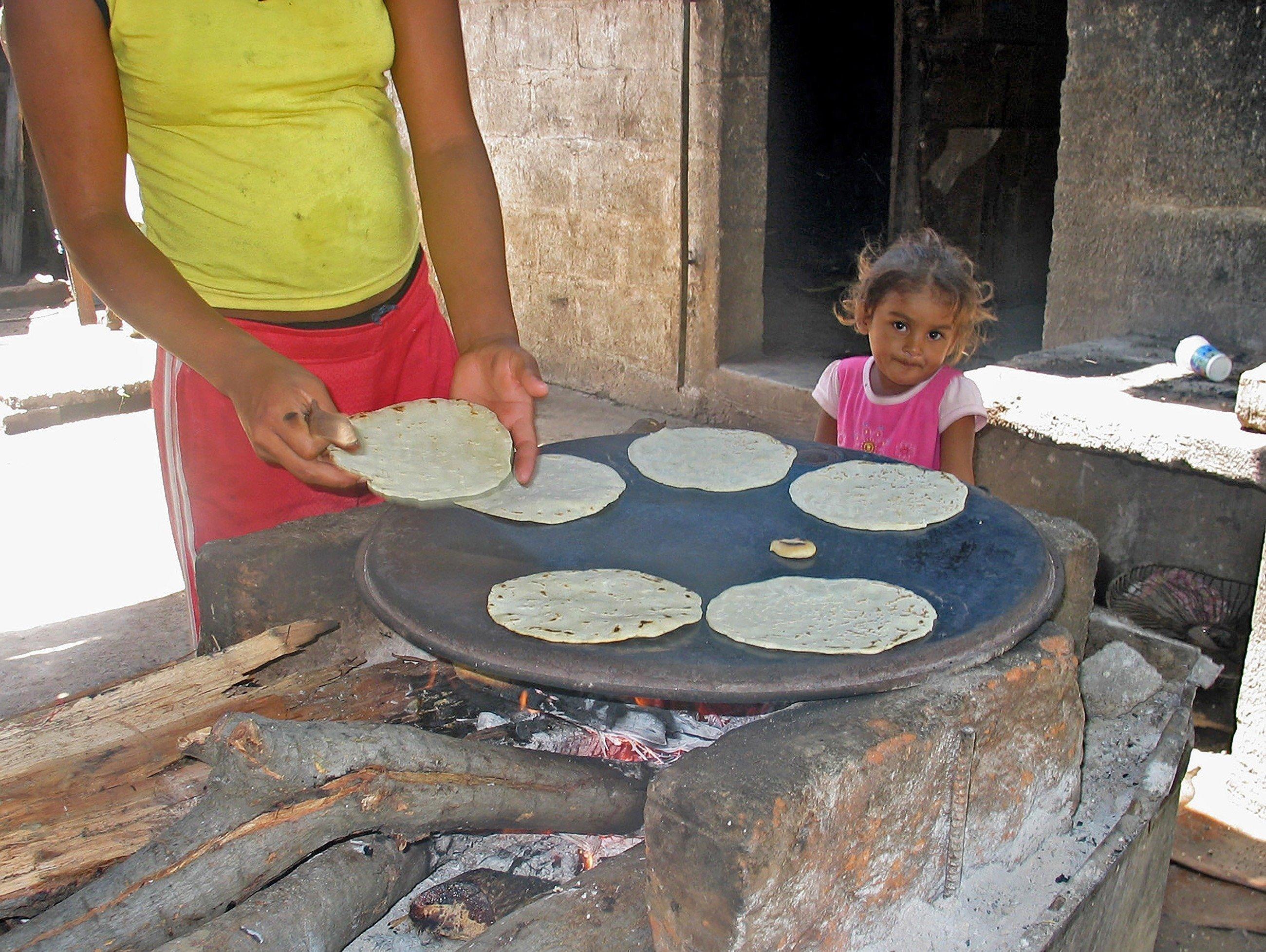 Ragazza osserva la madre intenta a preparare il pane.
