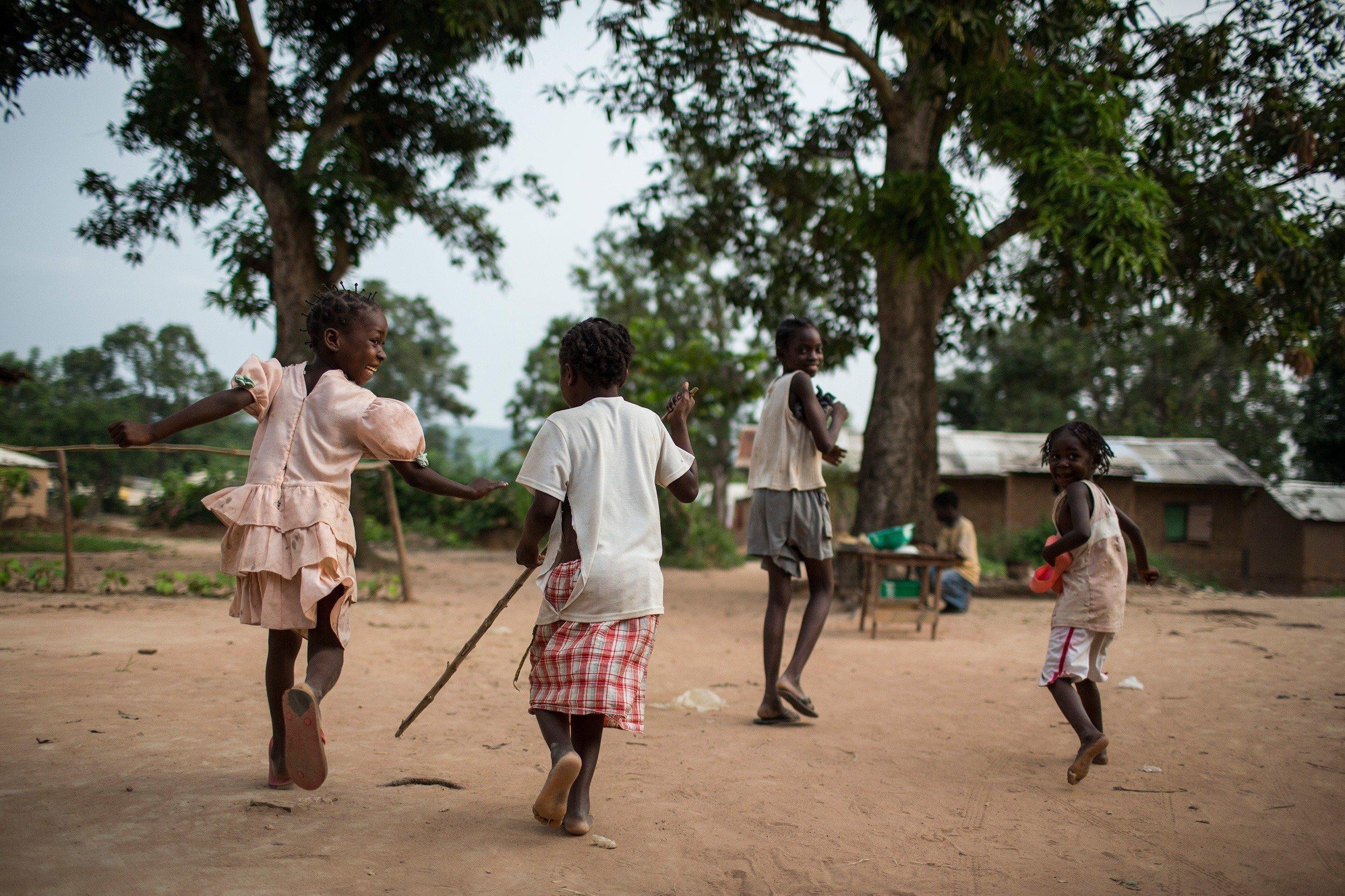 Bambini africani giocano a rincorrersi e prendersi.