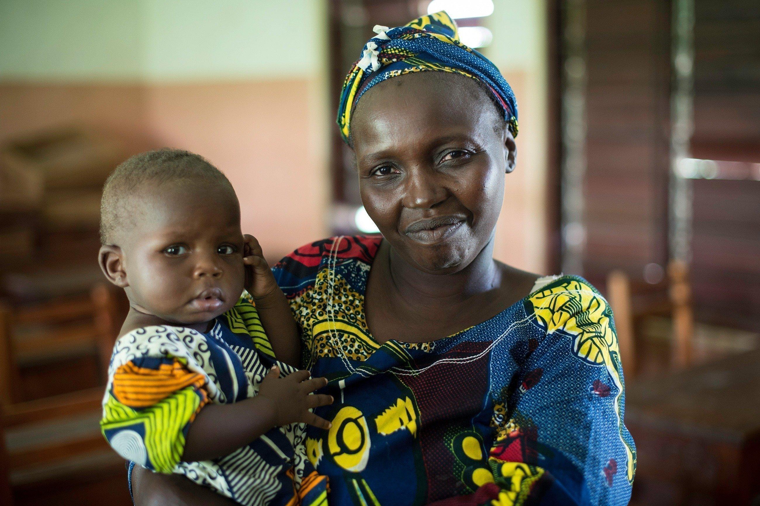 Madre SOS con un bambino in braccio.