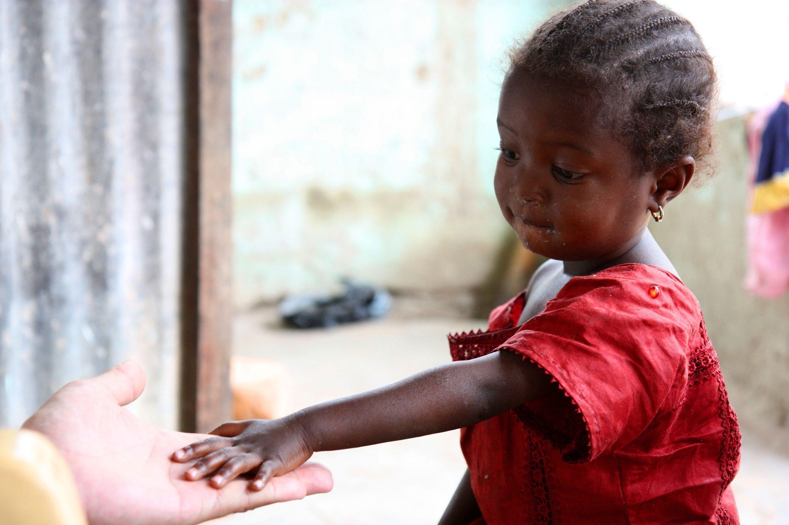 Una bambina africana tende la mano a un padrino.