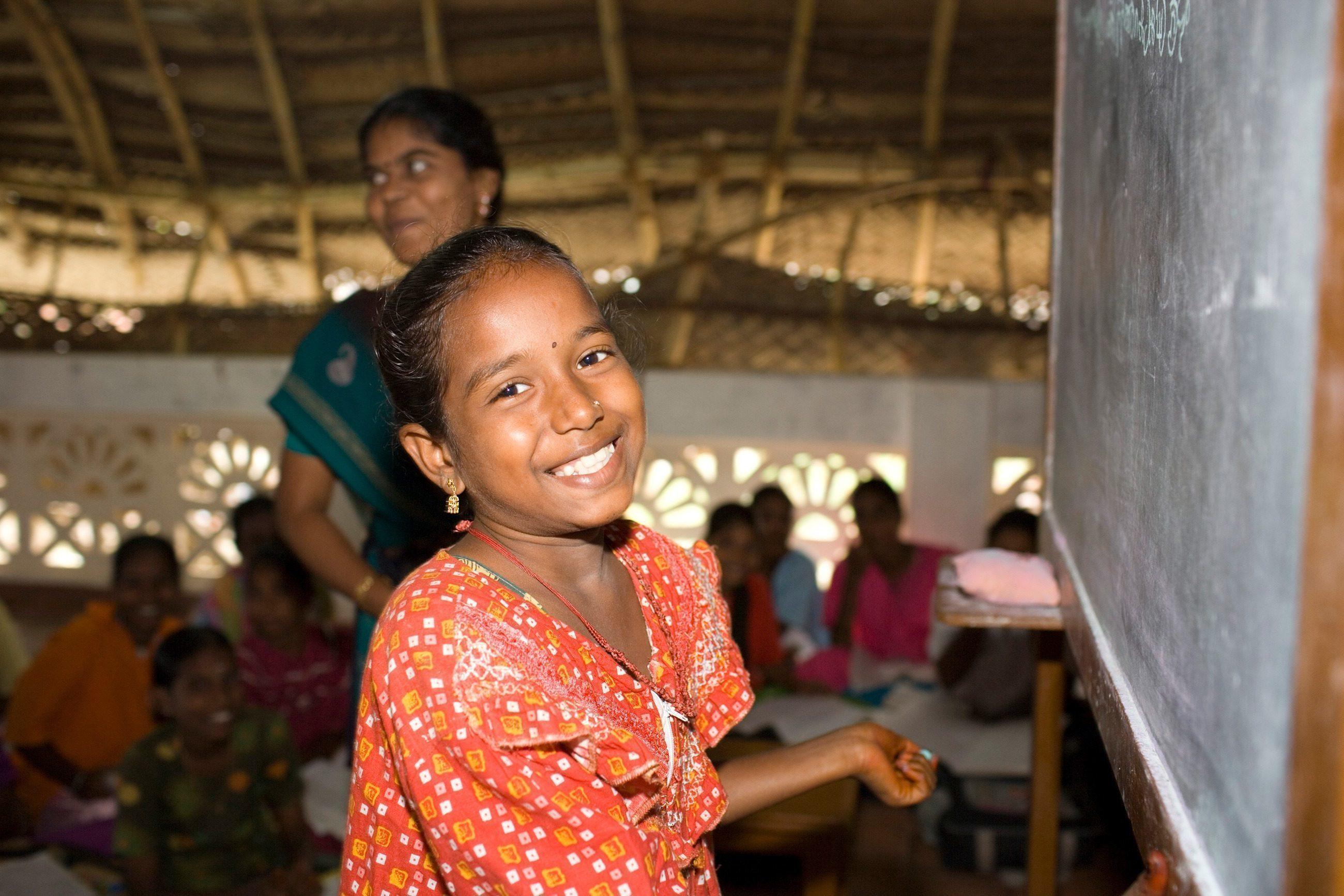 Una bambina indiana sorridente alla lavagna.