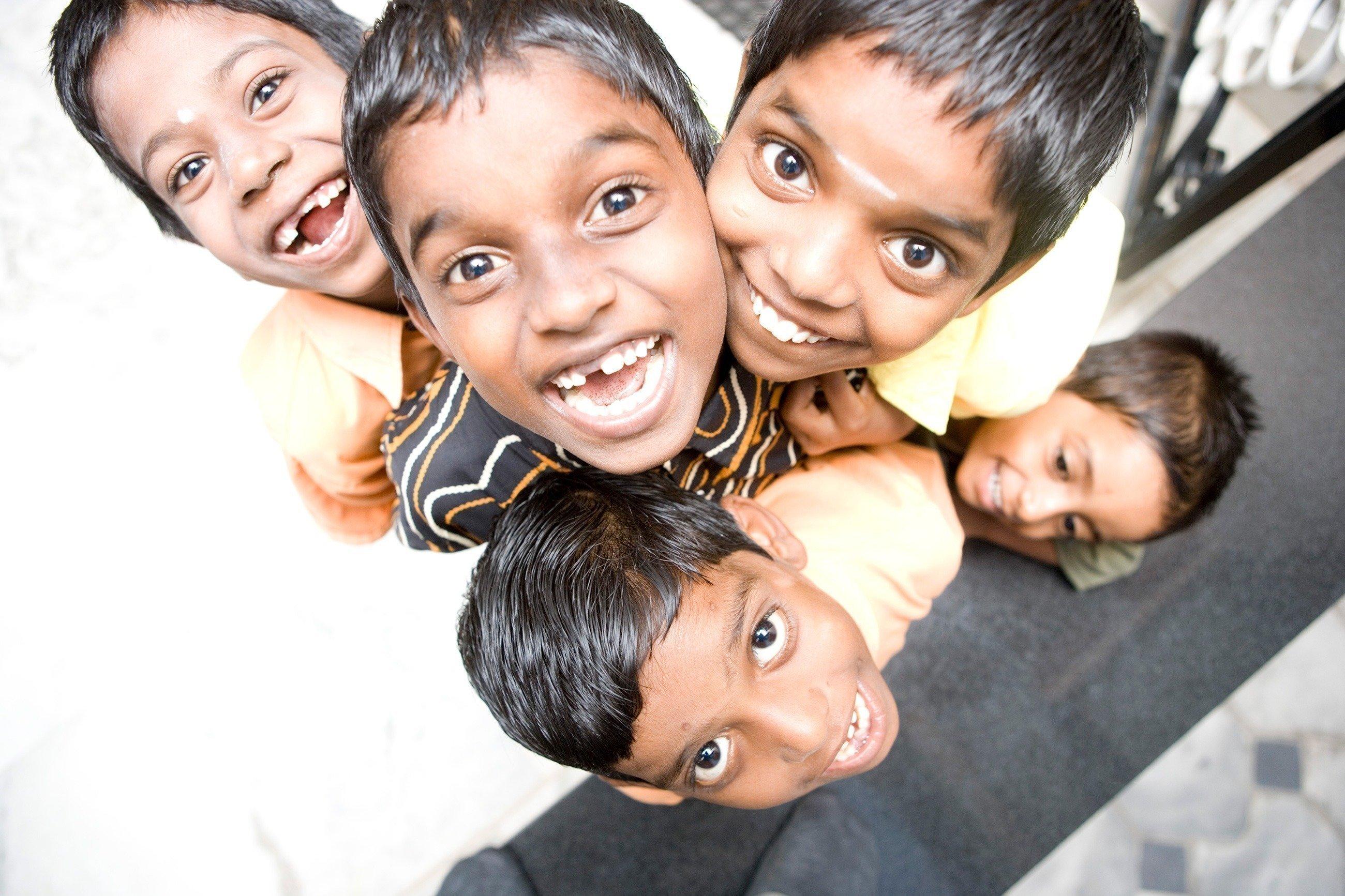 Bambini indiani sorridenti guardano in alto verso l'obiettivo.