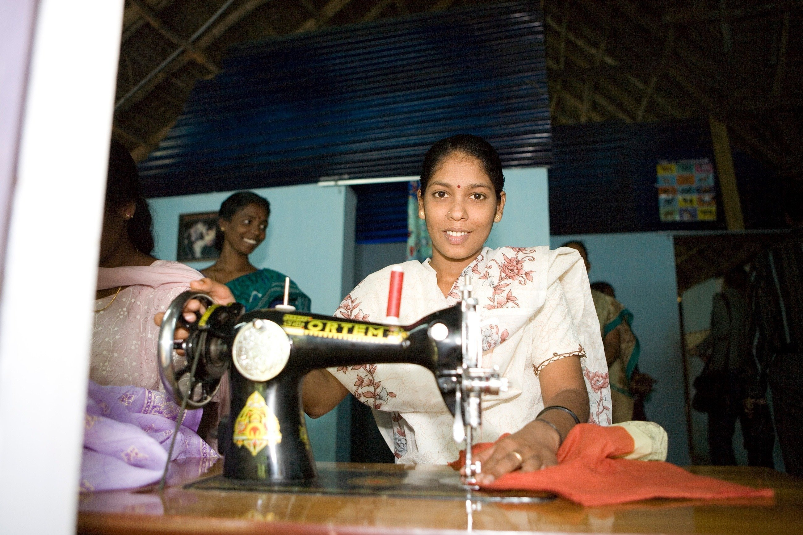 Una donna indiana intenta a cucire.