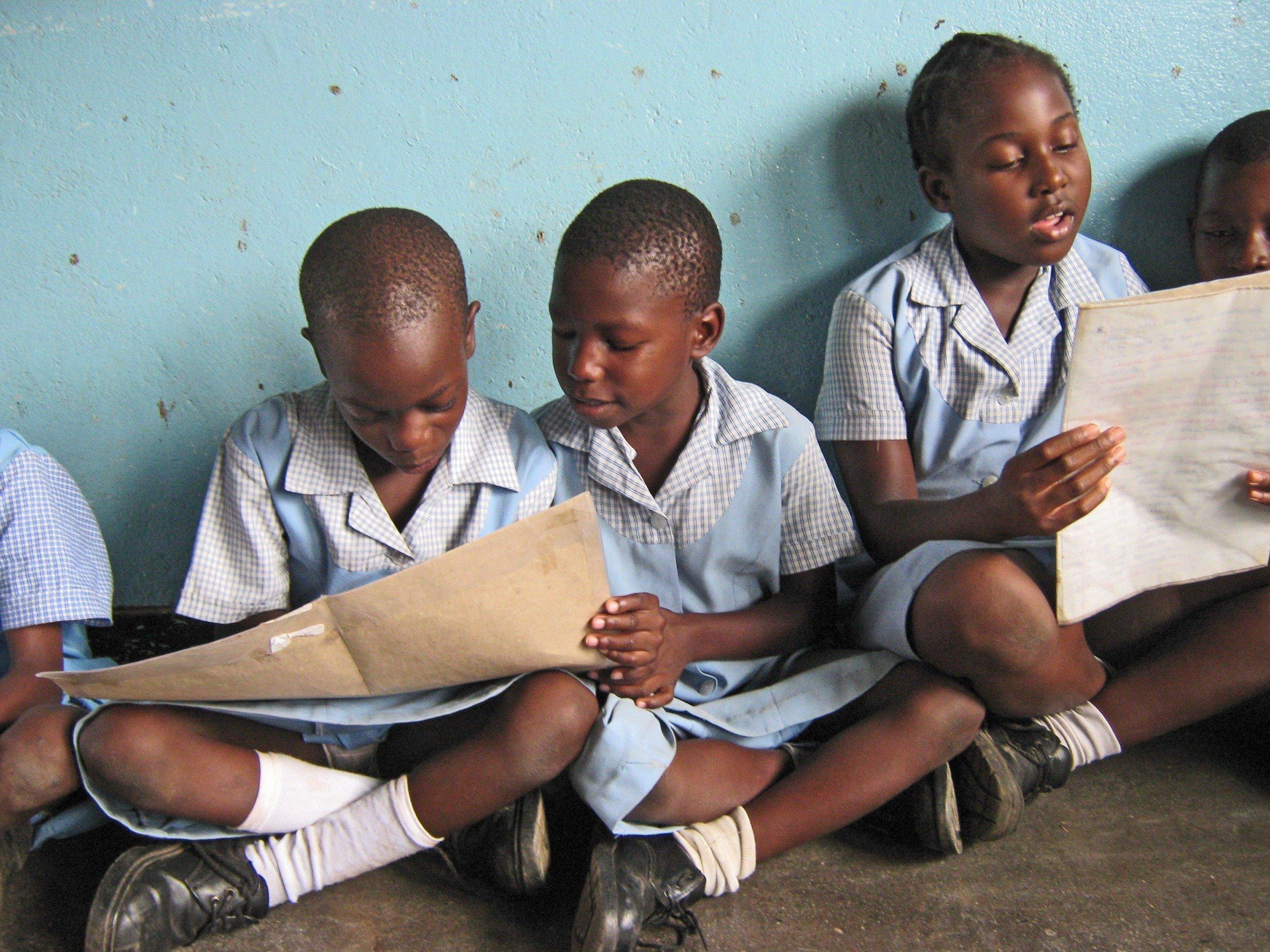 Bambine con abito blu leggono in un quaderno.