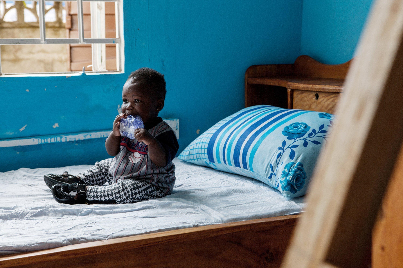 Ragazzino africano siede sul letto e mastica un pezzetto di plastica.