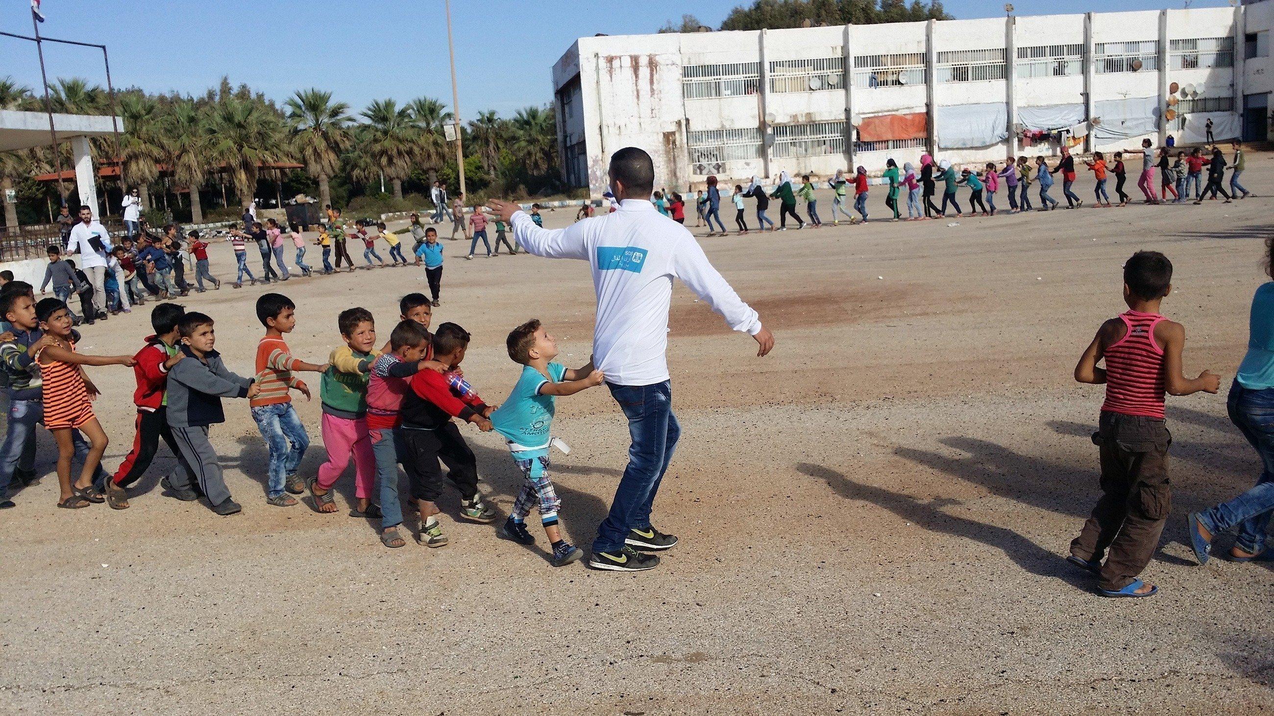 Un collaboratore di SOS Villaggi dei Bambini balla la polonaise insieme ai bimbi.
