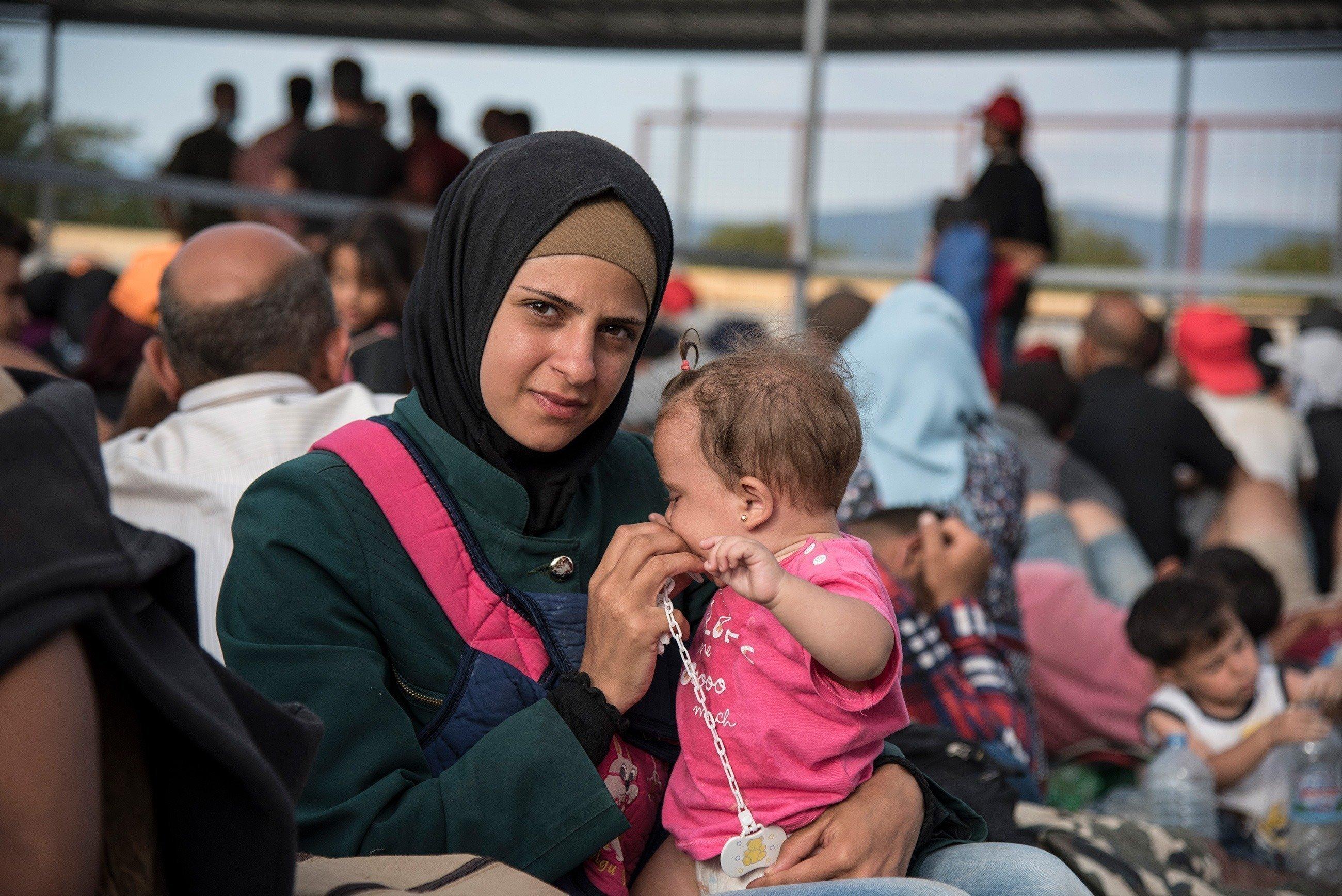 Una madre con in braccio la figlioletta.