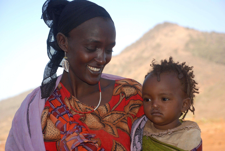 Una mamma SOS con un bambino piccolo in braccio.
