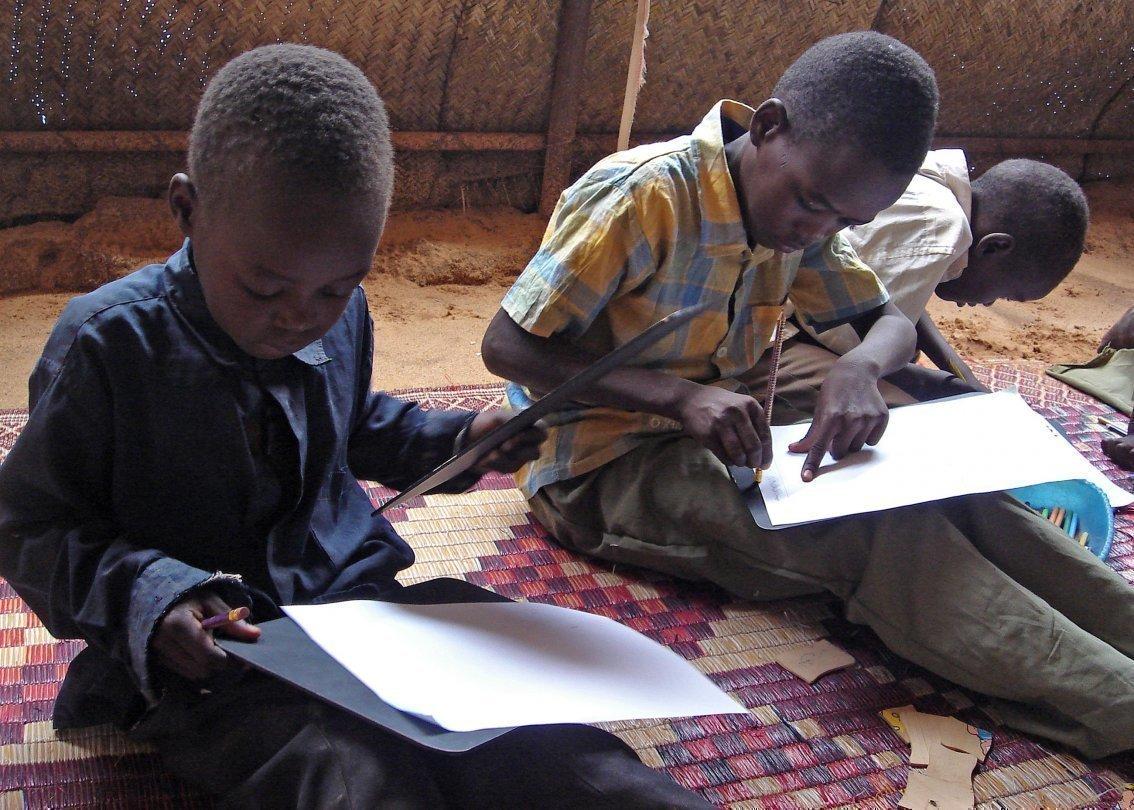 Due ragazzini in un villaggio dei bambini SOS seduti per terra leggendo nel loro quaderno