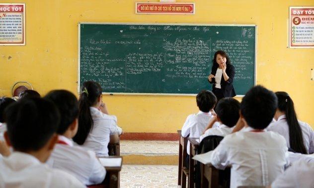 Eine Lehrkraft unterrichtet an der Tafel.