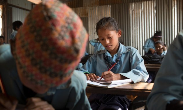 Mädchen schreibt in der Schule.
