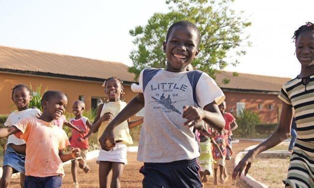 Bambini di SOS Villaggi dei Bambini mentre giocano a calcio.