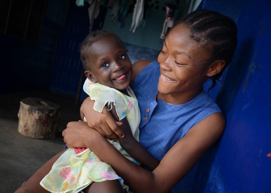 Una mamma africana SOS Villaggi dei Bambini con in braccio un bambino sorridente.