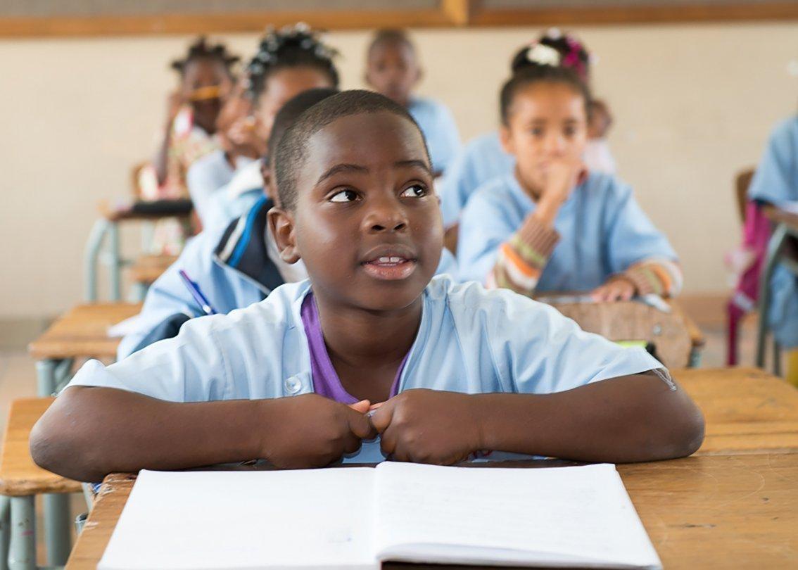 Un bambino africano seduto al banco di una scuola in un villaggio dei bambini SOS.