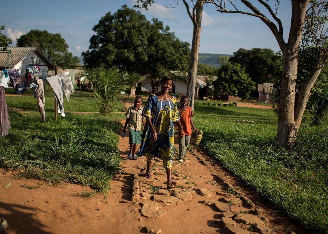 Una mamma che passeggia con i bambini in un villaggio dei bambini SOS in Africa.