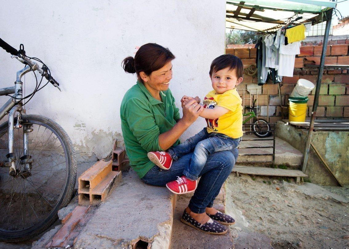 Madre con un piccolo bambino in grembo; entrambi ridono.