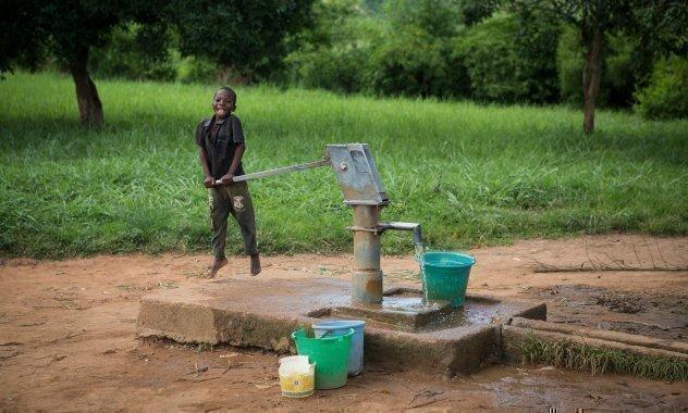 Bambino pompa acqua dal pozzo