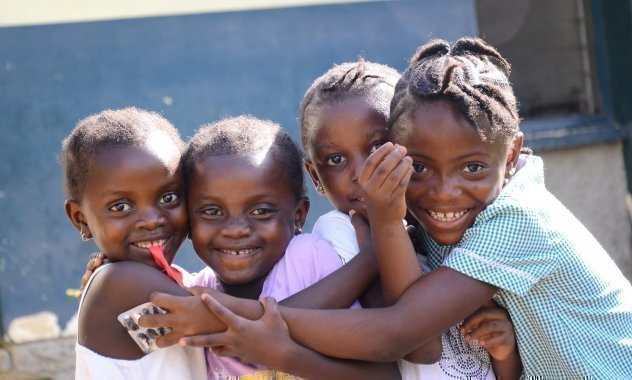 Quattro ragazzine africane allegre che si abbracciano