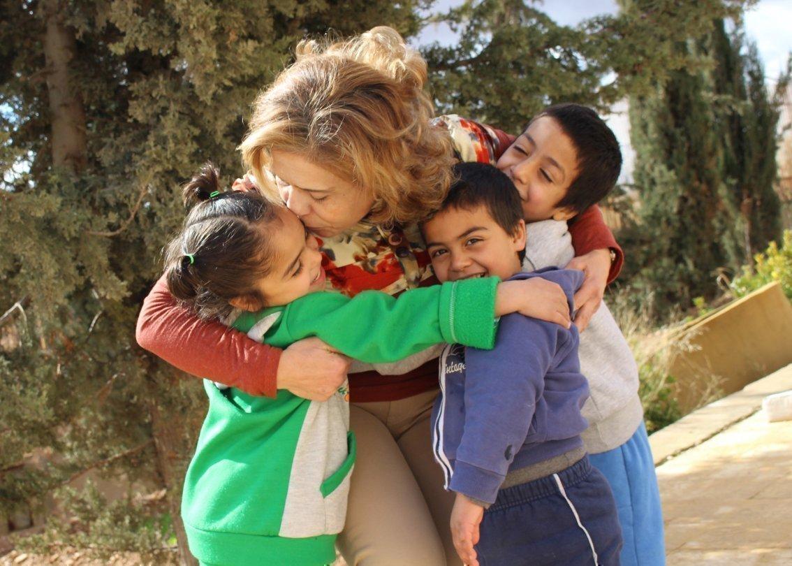Collaboratrice SOS Villaggi dei Bambini abbraccia tre bambini