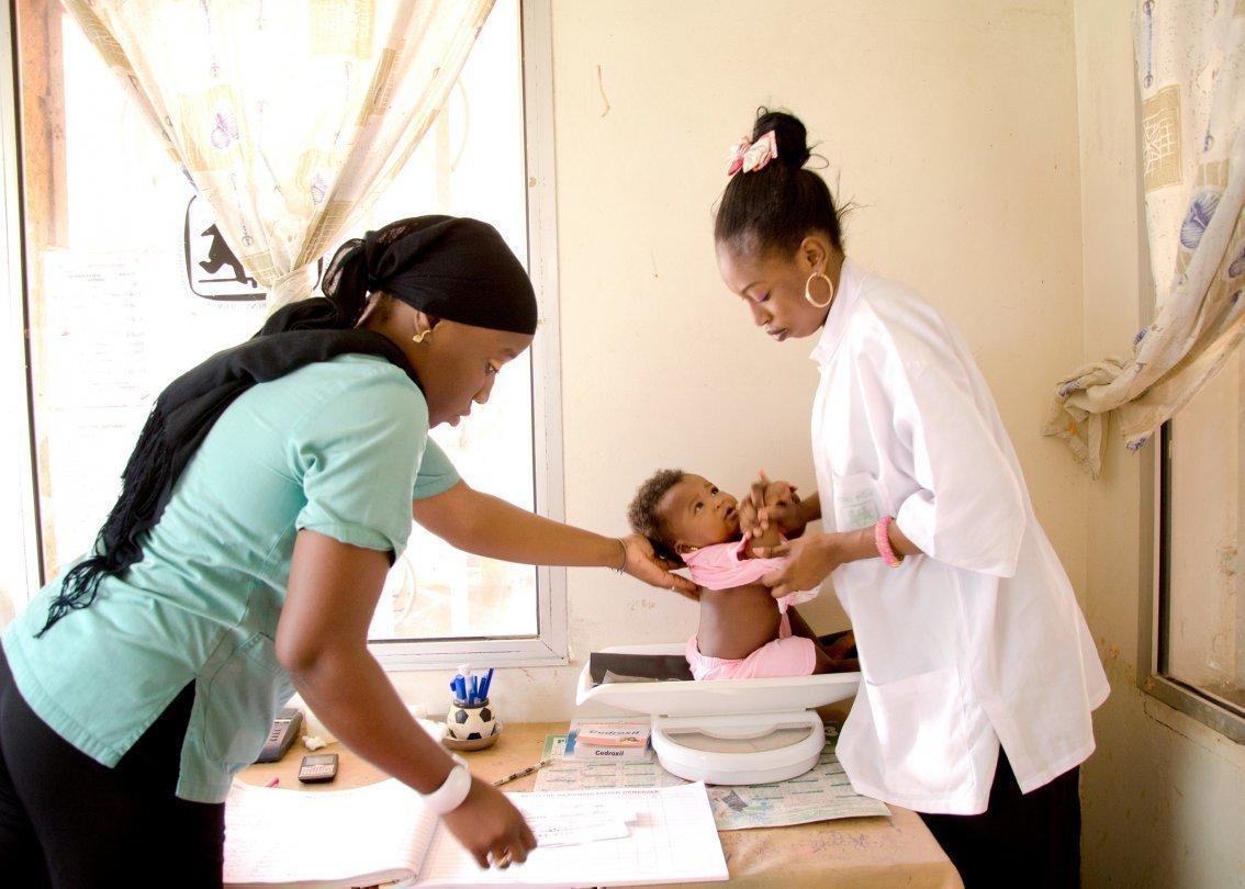 Infermiere pesano un bebè in un SOS Villaggio dei Bambini in Africa