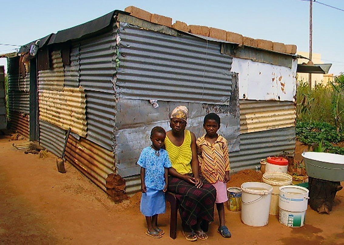 Mamma e due figli africani davanti a baracca