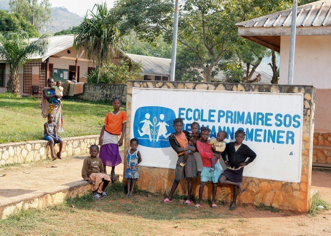 Bambini di un villaggio dei bambini SOS di fronte al cartello del villaggio.