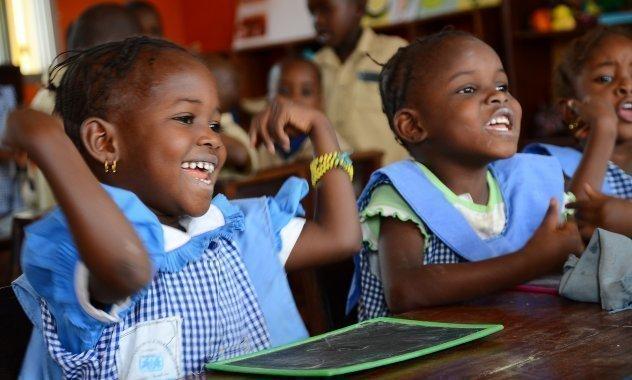 Due bambine a scuola si divertono mentre studiano.