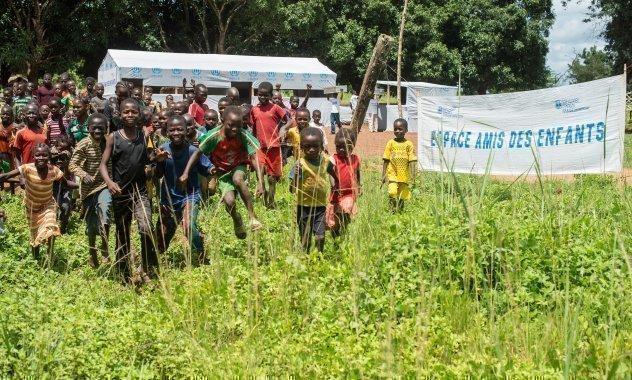 Un gruppo di bambini corre verso la telecamera. Un cartello d'ingresso mostra uno slogan di SOS Villaggi dei Bambini.